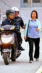 報道陣を前にひったくりの実演をする警察官。車道側にかばんを持つと狙われやすい=2013年4月11日、豊見城市・県警察運転免許センター