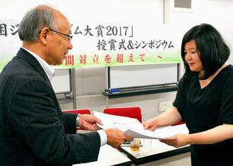 宇都宮健児さん(左)から賞状を受け取る高崎園子記者=11日、東京都渋谷区・東京ウィメンズプラザ