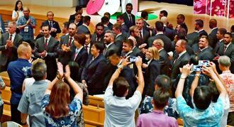 キャンプ地の読谷村関係者らから大きな拍手で迎えられる米国代表=18日、読谷村文化センター