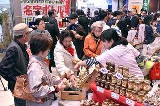 開幕と同時に多くの来場者でにぎわう久米島の物産コーナー=7日午前、那覇市久茂地・タイムスビル