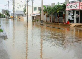 (写図説明)大雨の影響で冠水した道路=23日午前10時すぎ、石垣市真栄里
