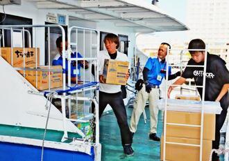 出発前の離島船舶で物資を詰め込む業者ら=11日、石垣港