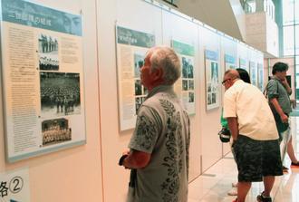 ハワイ移民の戦争体験などを紹介するパネルを見る来場者=5日、那覇市久茂地のタイムスビル