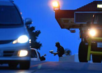 米軍普天間飛行場に出入りする車両をチェックする米兵=7日午後7時半、宜野湾市大山(国吉聡志撮影)