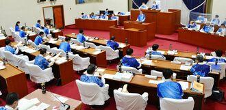 横浜DeNAベイスターズのユニホームを着る議員や市幹部=2月26日、宜野湾市議会