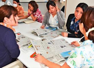 新聞を読み、気になる記事を話し合う社員ら=5日、那覇市の住太郎ホーム