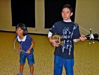 コザ物語の劇の一部を演じる仲宗根優河君(右)と上地野愛さん=8日、市文化センター