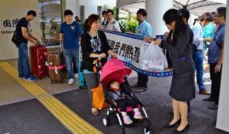 横断幕や記念品で出迎えを受ける台湾からの観光客=南ぬ島石垣空港国際線ターミナル