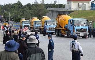 米軍キャンプ・シュワブに続々と入る工事車両に向かい、抗議する市民ら=18日午後0時50分、名護市辺野古