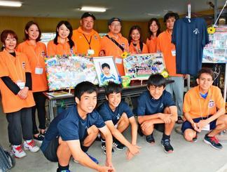 会場に飾られた手作りのボードを前に写真に納まる(後列左3人目から)栗山有希子さん、島袋広幸監督、栗山美昭さんら運営メンバー