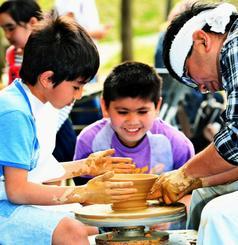 ろくろを回し、陶器作りを体験する子どもたち=31日、浦添市民体育館前(田嶋正雄撮影)