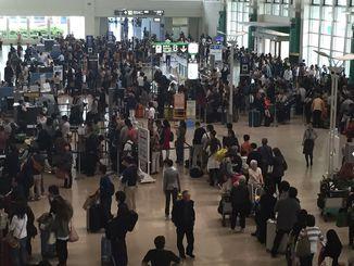 チェックイン手続きを待つ客で大混雑=22日午前10時半ごろ、那覇空港