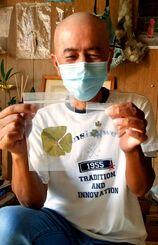 六つ葉のクローバーと、直径13センチの四つ葉のクローバーを持つ上江洲築さん。感染症予防のためにマスクが欠かせない=那覇市の自宅