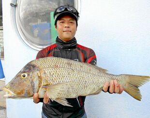 安良波ビーチで68センチ、3・3キロのタマンを釣った新垣雄一郎さん=7日