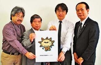あわもりこうじくんをPRする平良東紀さん(右から2人目)、安田正昭委員長(同3人目)ら=23日、沖縄タイムス社
