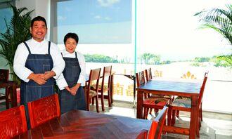 海が見える「琉球カレー喜美島南国亭」で、オーナーシェフの上谷喜美夫さんと、みち代さん夫妻=3日、糸満市摩文仁