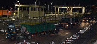 ブイなどの関連資材を積み、キャンプ・シュワブに入る大型トレーラー=20日午前2時30分すぎ、名護市辺野古(国吉聡志撮影)