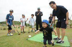 【2】心地よい風に吹かれながら、パークゴルフを楽しむ家族=南城市の大里城趾公園