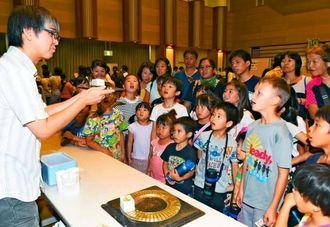 磁石と液体窒素を使った超伝導実験に興味津々の子どもたち=6日午後、ちゃたんニライセンター