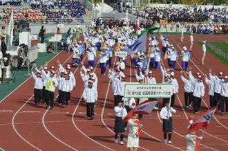 スタンドの声援に笑顔で応える沖縄県選手団=24日、和歌山県紀三井寺公園陸上競技場