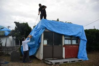 台風対策でプレハブにブルーシートを被せる住人=16日午後6時38分、与那国町祖納集落