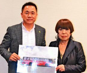 「東京五輪応援ラッピングバス」の写真を手に「皆で盛り上げましょう」と呼び掛けるコシノジュンコさん(右)と同バスを企画した赤坂守さん=9日、沖縄タイムス社