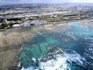 西海岸開発が予定されるキャンプ・キンザー(中央奥)の沿岸海域(手前)。間にサンエー浦添西海岸パルコシティがある=2019年11月、浦添市西洲