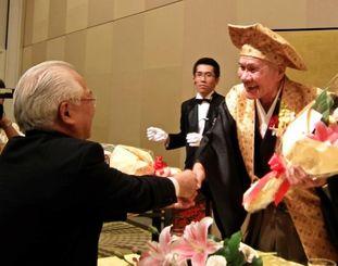 関係者から祝福の花束を贈られる田中旨夫医師(右)=26日、宜野湾市真志喜・ラグナガーデンホテル