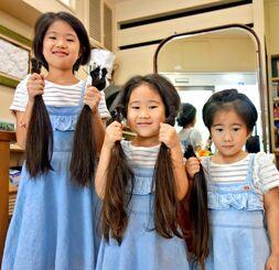 おそろいの服装で、カットした髪の毛をそれぞれ手にする(左から)宇江城くるみさん、このみさん、かなみちゃん=8月25日、那覇市久茂地の美容室「カットスタジオ21」