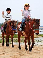与那国馬に乗って気持ちよさそうに浜辺を散策する子どもたち=12月30日、南城市玉城・百名ビーチ