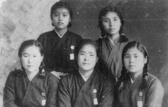 制服を着て友達や先輩と並ぶ島袋淑子さん(前列右)。制服の胸には住所、氏名、血液型を書いた名札を縫い付けていた=1943年(ひめゆり平和祈念資料館提供)