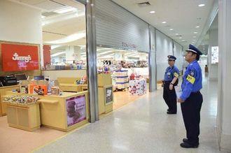 台風で閉館となるため土産品売り場のシャッターを下ろす警備員=3日午後1時20分、那覇空港