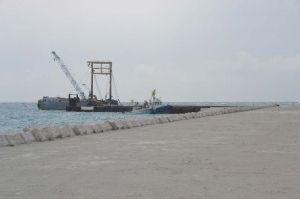 完成した仮設桟橋(奥)からクレーン車を降ろす運搬船と仮設道路(手前右)=16日、那覇空港滑走路増設予定地沖合