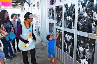 写真展「あんやたん農連市場」の作品を鑑賞する人たち=8日、那覇市樋川の農連市場
