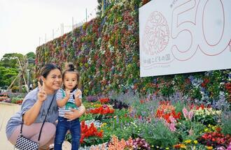 「花まつり2020」で展示されているフラワーウオールに笑顔の親子連れ=20日、沖縄市胡屋・沖縄こどもの国