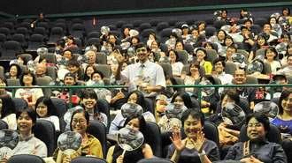 観客と手を振って撮影する満島真之介(中央)さん=18日午後、那覇市・シネマQ