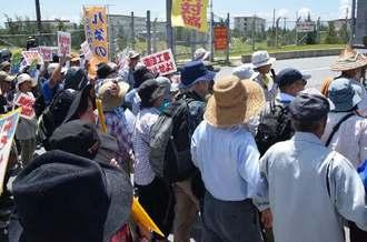 米軍キャンプ・シュワブゲート前で「違法工事を中止せよ」とシュプレヒコールをする市民ら=22日午前10時47分、名護市辺野古