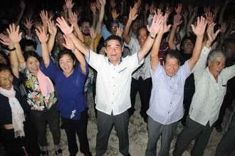 多良間村長選で2期目の当選を決め、支持者とバンザイ三唱で喜ぶ伊良皆光夫氏(中央)=25日午後8時49分、多良間村塩川の後援会事務所前