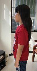 髪を切る直前の比屋根義章さん。腰の上まで伸びた(提供