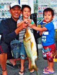 西崎海岸で64・7センチ、3・17キロのタマンを釣った仲間寛和さん(左端)=5月28日