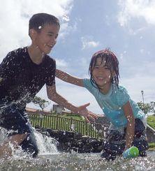 青空の下、元気に水遊びをする子どもたち=8日午後、うるま市・倉敷ダム