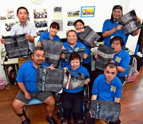 シートベルトを再利用したバッグを手にする障がい者就労支援センターすばるの作業員と、琉球ブリッジの谷中田洋樹代表(後列左)=浦添市城間