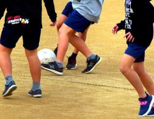 55日ぶりに使用が再開された運動場でサッカーをする子どもたち=6日午前、宜野湾市・普天間第二小学校