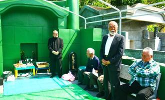 恩師の墓の改築を祝いあいさつする安仁屋宗八さん(右から2人目)=読谷村渡具知