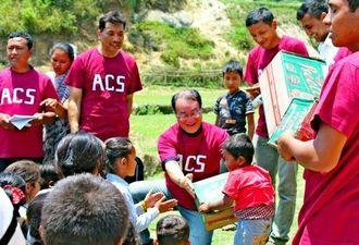 不公平がないようにと集まった児童一人一人に支援物資を手渡すアジアチャイルドサポート(ACS)スタッフら。中央は玉木馨専務理事=5月22日、ネパール・マハンカール小学校(ACS提供)