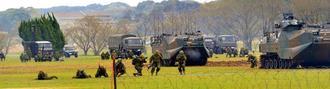 離島奪回訓練のデモンストレーションで水陸両用車AAV7(後方)で上陸し、前進する水陸機動団員
