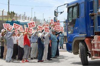 「新基地反対」「埋立阻止」のプラカードを工事車両に掲げて、反対を訴える市民ら=7日午前10時40分ごろ、名護市辺野古・米軍キャンプ・シュワブ前