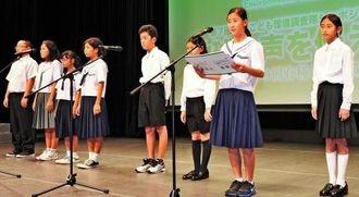 環境保全へのメッセージを読み上げる沖縄こども環境調査隊のメンバー=5日午後、那覇市久茂地のタイムスホール