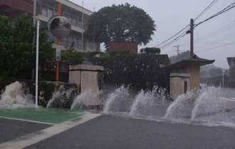 伊江村役場前では大雨で排水溝から水が噴き出した=16日午前