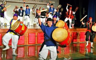 東北出発を前に力強い演舞を披露する北中城村東北エイサープロジェクトのメンバー=7月30日、北中城村中央公民館